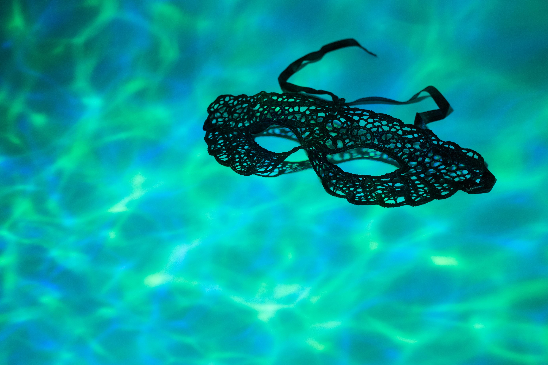 Schwarze Spitzenmaske schwimmt im Pool